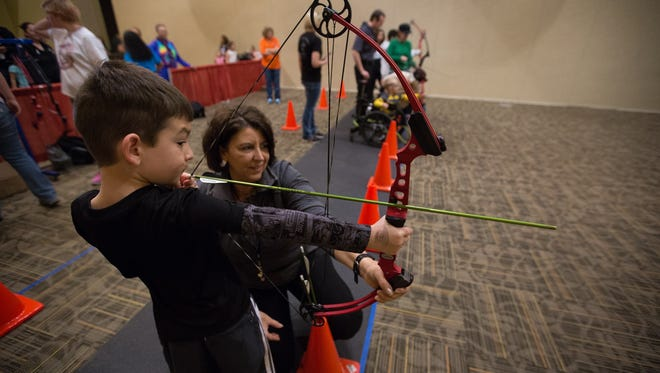 """Carlos """"CJ"""" Parra,7, draws an arrow back with help and advice from Michaela Wolfe, with New Mexico Game and Fish, in the archery range at the Mesilla Valley Outdoor Expo, Saturday January 14, 2017 at the Las Cruces Convention Center."""