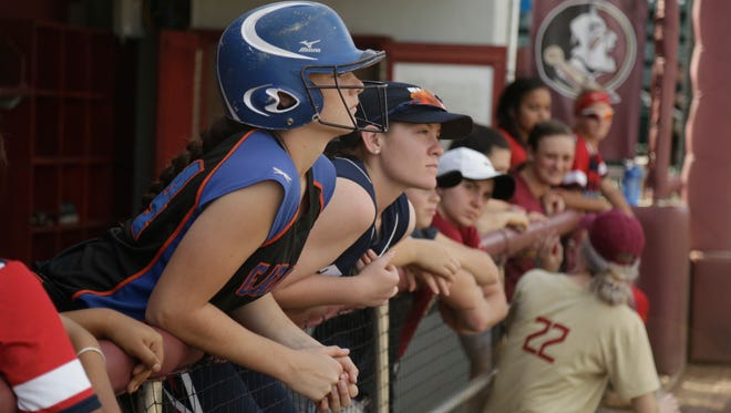 Suncoast Community High freshman Reagan Conley, 14, watches a scrimmage from the dugout during Sunday's softball camp hosted by Florida State in honor of Monk Bonasorte.