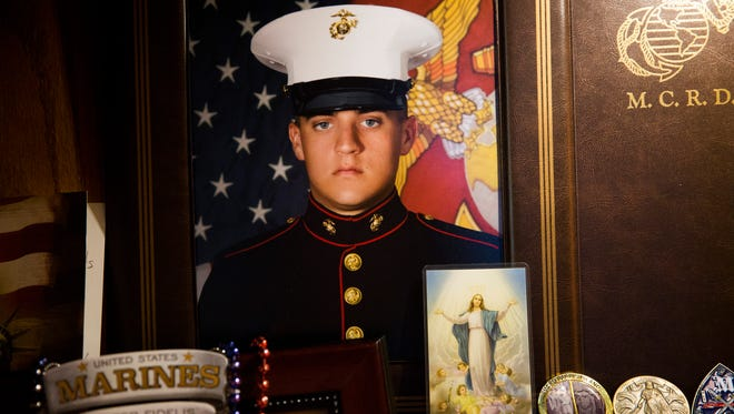 A portrait of United States Marine Austin Ruiz sits inside a cabinet in his parent's dining room Tuesday, Jan. 17, 2017 in Golden Gate Estates. Ruiz was killed Friday, Jan. 13, 2017 during a Marine training exercise in Twentynine Palms, California.