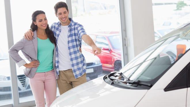 A couple at a car dealership.