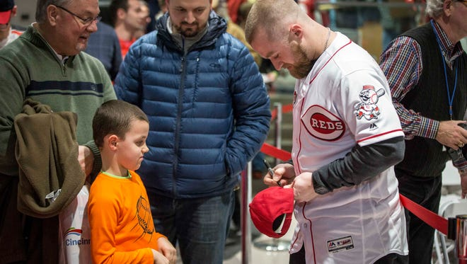 Cincinnati Reds catcher Tucker Barnhart signs a hat for a fan in line at the annual Reds caravan event Thursday, Jan. 26, 2017 at Stoops Automotive. Muncie was one stop across five states that the team visited.