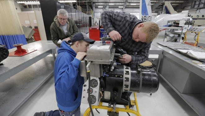 Josh Faude, left, and Kevin Arneson try to get a part off an auxiliary power unit as Pete Winkelmann looks in a manual at Fox Valley Technical College's S.J. Spanbauer Aviation and Industrial Center in Oshkosh. A new program administered by the University of Wisconsin Oshkosh aims to support exports in targeted industries, like aviation.