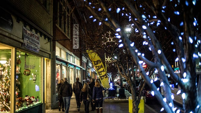 People walk along the storefronts on Huron Avenue during the Chilly Fest Cocoa Crawl Friday, Jan. 27, 2017 in downtown Port Huron.