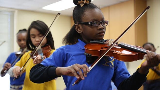 Fourth-grade students at Apalachee Elementary School practice violin in their classroom Monday.