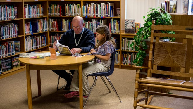 Tutor David Korff, of Port Huron, reads a book with Annabelle Crowe, 7, during the Read for Life after-school program Wednesday, Feb. 1, 2017 at Woodrow Wilson Elementary School in Port Huron.