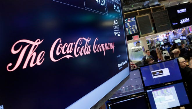 The Coca-Cola logo appears above the post where it trades on the floor of the New York Stock Exchange, Friday, Dec. 9, 2016. Coca-Cola said Friday that CEO Muhtar Kent will step down as CEO next year and be replaced by Chief Operating Officer James Quincey. (AP Photo/Richard Drew)