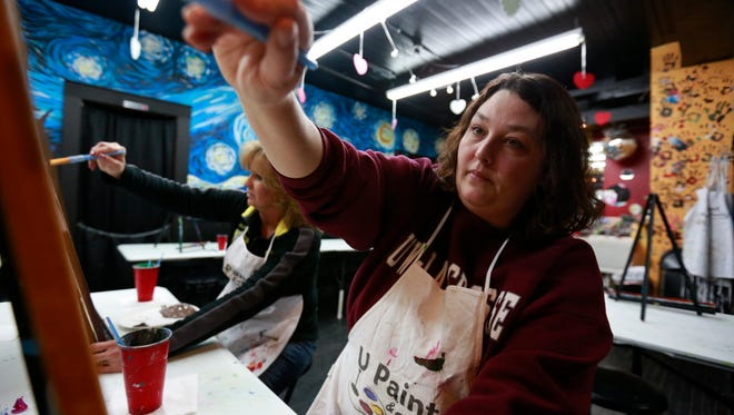 Sara Clark, of Merrill, works on her oil painting during Wednesday night's painting class at U Paint & Party in Wausau.