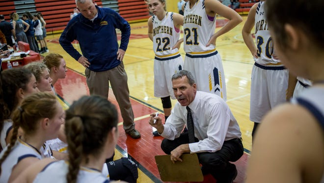 Port Huron Northern coach Mark Dickinson talks with players in a time out during a district semifinal basketball game Wednesday, March 1, 2017 at Anchor Bay High School.