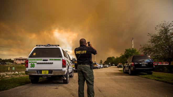 Sgt.Patrick Lawson takes photos with his phone as a brush fire continues to burn in eastern Collier County on Tuesday, March 7, 2017. Mandatory evacuations were ordered and Golden Gate Community Center is prepared to take people in who need shelter.