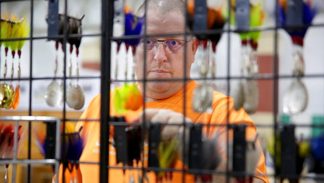 Trygve Smalley, an employee with Skimmer Lures and Guide Service in Milwaukee, works on hanging lures at the company's booth at the Milwaukee Journal Sentinel Sports Show.