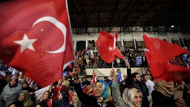 Supporters of the Turkish President Recep Tayyip Erdogan wave Turkish flags and shout slogans as the Turkey's Prime Minister Binali Yildirim addresses voters during a rally to shore up support for a 'yes' vote in next month's referendum in Turkey on expanding presidential powers, at a stadium in Nicosia, Cyprus, on March 9, 2017.