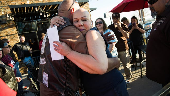 Cecilia Mata, hugs Jesus Ortega, president of the Embudo motorcycle club at Wing Daddy's, Friday March 10, 2017 after Mata who is currently battling cancer received donations from six motorcycle clubs to help her.