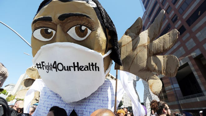 An oversize effigy of a health care professional is seen as hundreds of people march through downtown Los Angeles protesting President Donald Trump's plan to dismantle the Affordable Care Act, his predecessor's signature health care law, Thursday, March 23, 2017. The demonstration came as U.S. congressional leaders postponed a vote on the American Health Care Act, which the White House hopes will replace Obamacare. (AP Photo/Reed Saxon)