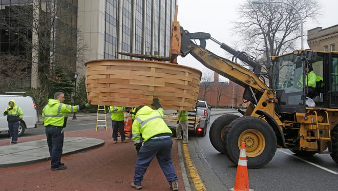 City of White Plains workers and contractors replaced a giant flower basket on South Broadway and Armory Place in White Plains on Tuesday. The original was heavily damaged in a car accident last year.
