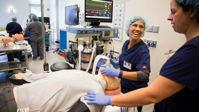 "Mary Zavicar practices mask ventilation on ""Manny"" the mannequin, with the help from Kathy Minott, faculty at Wolford College, in the laboratory on Wednesday, March 29, 2017, at Wolford College in North Naples. Wolford trains students to become nurse anesthetists by using simulation mannequins."
