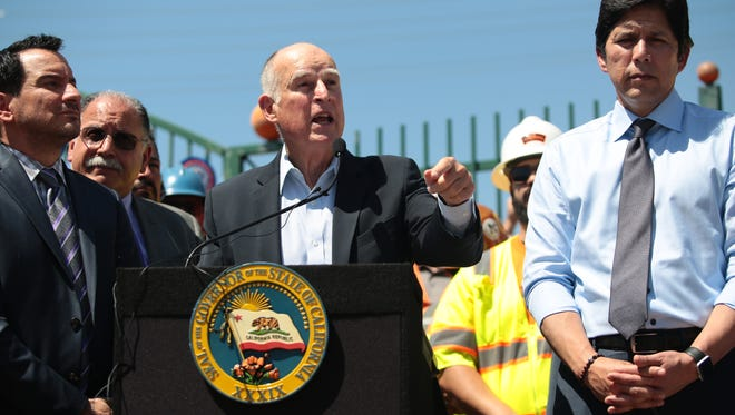 California Governor Jerry Brown speaks in Riverside on Tuesday, April 4, 2017, in support of the Road Repair and Accountability Act or SB 1, a 10 year, $52.4 billion road repair and transportation investment bill. Senate President pro Tem Kevin de Leon, right, and Assembly Speaker Anthony Rendon, left, are also pictured.