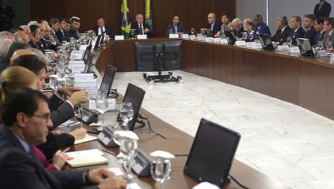 Brazil's President Michel Temer (center top) leads a meeting with agriculture and meat sector representatives.  Temer is holding several meetings in light of a recent corruption probe that revealed Brazilian meatpackers bribed inspectors to keep rotten meat on the market.