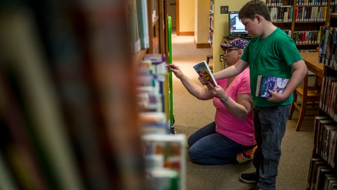 Kole Hammons, 7, looks over books with his mother, Kimberley Wills-Hammons, at the Moore Public Library in Lexington. Kole, who was adopted by Wills-Hammons, was diagnosed with fetal alcohol syndrome at nine-months-old. Kole has been enrolled in Cros-Lex's year-round schooling program, as a structured schedule helps him with his learning and behavioral struggles related to FAS. The district decided in February to end the program, which currently serves 337 students.