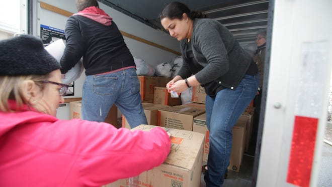 Pratima Vijayakumar, with Greater NYC Families for Syria, tapes up a box that is destined for Syria to aid refugees.