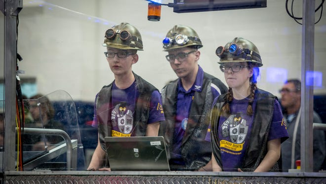 Mecanum Knights 3667 members Nolan Odon, 14, left, Connor Jawor, 15, and Olivia Hudson, 14, control their robot during a FIRST Robotics District Event on April 7, 2017 at Marysville High School.