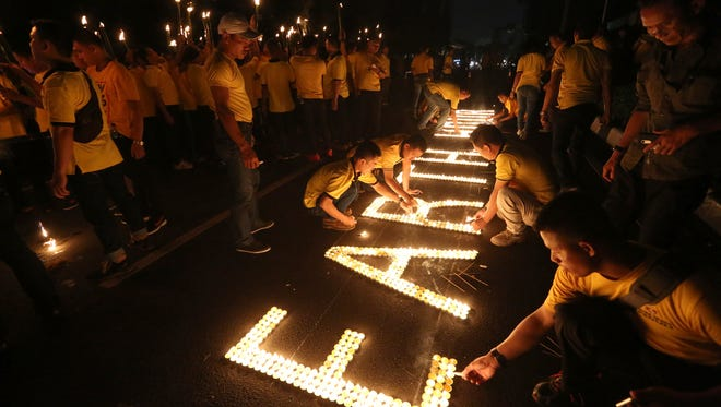 Activists light candles as buildings turn their exterior lights off for the Earth Hour at the main business district in Jakarta, Indonesia, Saturday, March 25, 2017. Earth Hour takes place worldwide and is a global call to turn off lights for 60 minutes in a bid to highlight the global climate change. (AP Photo/Tatan Syuflana)