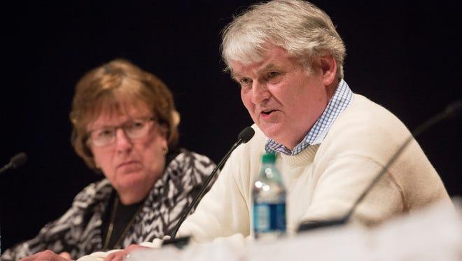 Muncie Community School Board members Debbie Feick and Andy Warrnner vote to close three schools Thursday night.