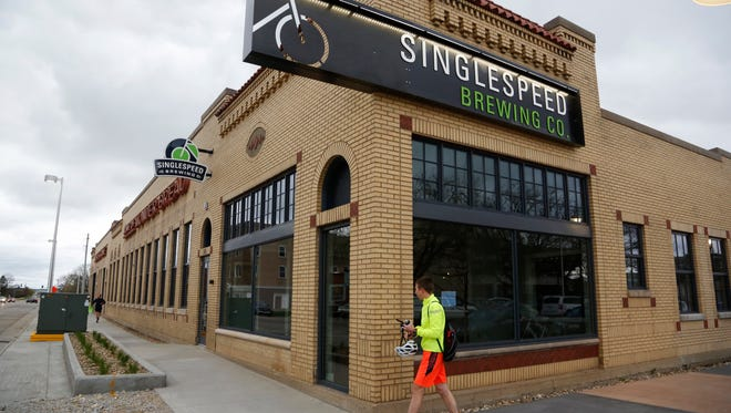 In this Thursday, April 20, 2017, photo, a man walks near the SingleSpeed Brewing Co. in the former Hostess Wonder Bread building in Waterloo, Iowa. A once crumbling bakery in Waterloo that for decades produced Hostess Wonder Bread is now opening as a brewery, restaurant and distribution center. (Matthew Putney/The Courier via AP)