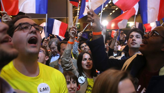 Supporters of French centrist candidate Emmanuel Macron react at his election day headquarters in Paris on April 23, 2017.