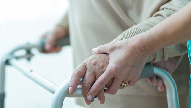 A woman using a walker is assisted by a caregiver.