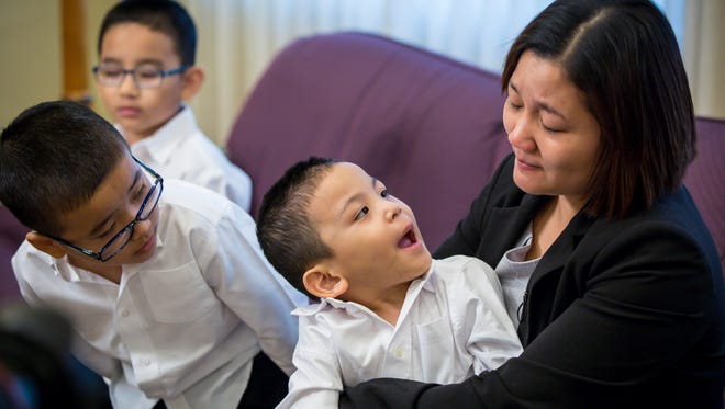 Ester Kim, widow of Stephen Kim, who was killed in an April 21 shooting, tears-up while talking about their family Friday, April 28, 2017, at the Caldwell Parrish Funeral Home in Urbandale with her sons, Martin, 4, holding, David, 6, middle, and Joseph, 8, far left.  Stephen Kim, 41, of Des Moines,was killed after an attempted robbery went wrongwhile he was waiting in his car for his wife, who was carpooling to meet him after work. He was killed while his three sons — allunder the age of nine — were sitting in the back seat.