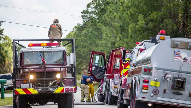 Fire and rescue workers work to contain a brush fire in Golden Gate Estates on Saturday, April 29, 2017.