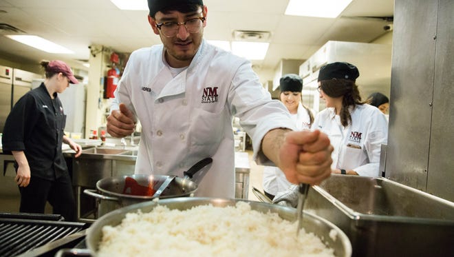 Andres Borrego, a student at 100 West Café at New Mexico State University, stirs rice before the lunch rush, Friday April 28,2017.