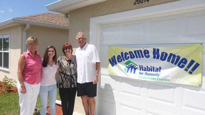 Susan Mulligan, left, Leah and Linda Leonard and Terry Mulligan stand in front of the Leonard's new Habitat for Humanity home.
