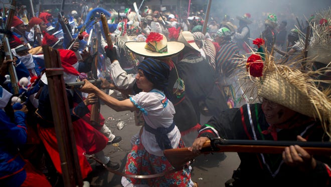 People take part in a re-creation of the Battle of Puebla in Mexico City on May 5, 2013.