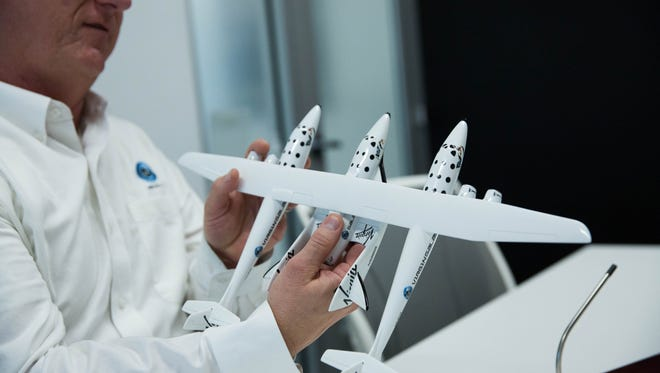 Pete Nickolenko, chief engineer for Virgin Galactic, uses a model of the WhiteKnightTwo to demonstrate the aircraft while in the operations area for the company's Las Cruces offices May 8, 2017.