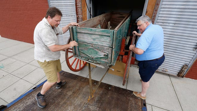 The History Museum received a donation of an original Springfield Wagon Henry's towing delivered it. executive History Museum Director John Sellars, right, and Eric Corey, carefully more the wagon into the museum.