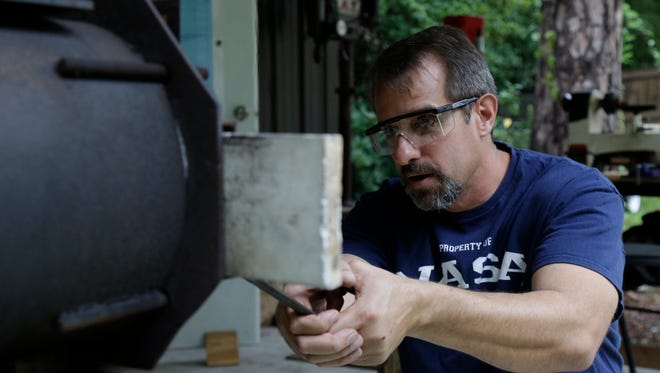 local bladesmith Dan Hurtado heats a blade he's working on in his home forge Sunday, May 21.