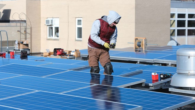 Erik Spoerle of SunBlue Energy, a Sleepy Hollow company, installs solar panels on the roof of a Westchester Day School building in Mamaroneck.