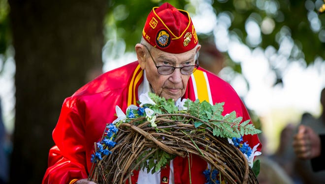 Veteran Dward McMillen, 84, of Des Moines, lays a wreath on the Korean War monument at a Memorial Day multi-war service at the Iowa State Capitol grounds Monday May 29, 2017, in Des Moines, Iowa.