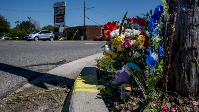 Flowers are displayed on a curb at the intersection of Garfield and Pine Grove Avenue in Port Huron. Two motorcyclists have died in crashes at the intersection in the past three years, and crashes have increased at the intersection since 2011.