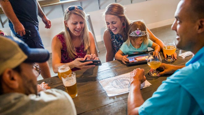 Lizzie Malaniak, left, and Makenzie Schutt, holding daughter Morgan, 2, of Estero, drink together at Palm City Brewing in Fort Myers on Saturday, June 3, 2017. The grand opening will be June 17.