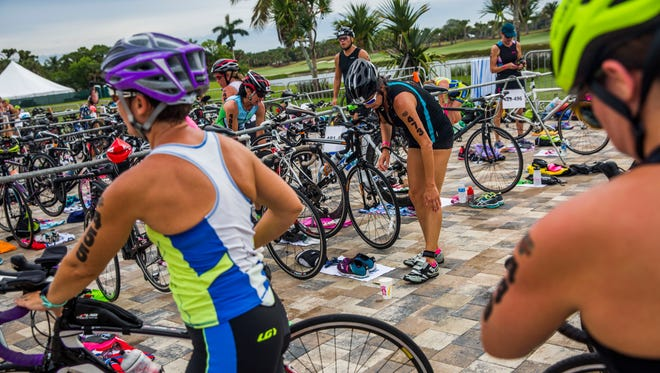Athletes transition from running to biking while competing in the 31st Annual Fitness Challenge Triathlon at Naples Beach Hotel and Golf Club on Sunday, June 4, 2017.