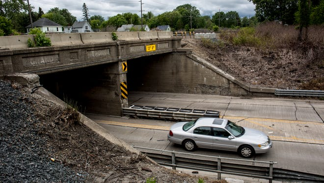 A vehicle passes under the railroad bridges on 24th  Street Tuesday, June 6, 2017 at the border of Port Huron and Port Huron Township. Canadian National Railroad has agreed to repair, paint and maintain the structure,