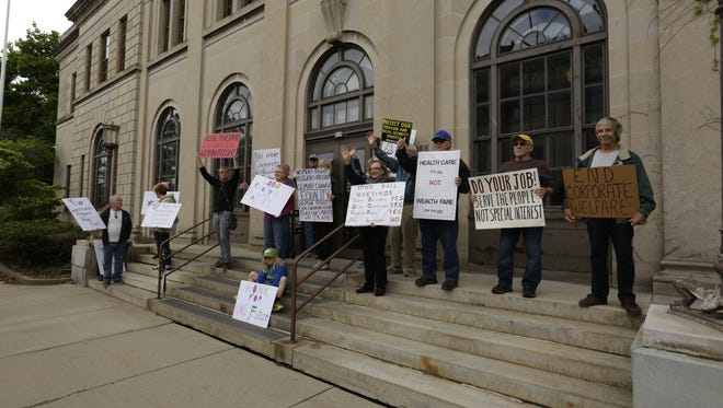 Protesters gather outside U.S. Sen. Ron Johnson's office for their weekly Tuesday protest. The Oshkosh Tuesday Rally Group has been meeting for the past 20 weeks.