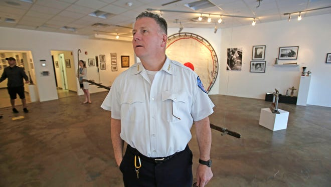 Yonkers Fire Department Deputy Chief Thomas Fitzpatrick looks at the exhibition at the Urban Studio Unbound gallery.