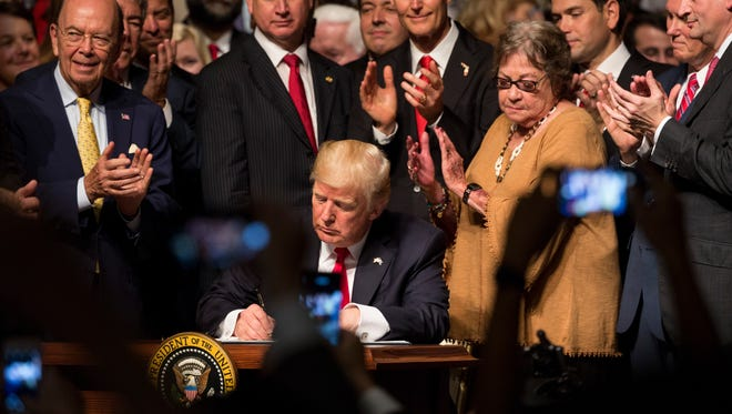 President Donald J. Trump signs his executive order regarding his Cuba policy on Friday June 16, 2017 in Miami, Florida, at Manuel Artime Theater. The executive order enforces a strict ban on tourism, calls for new reporting requirements for visitors, and institutes a ban on doing business with the military.