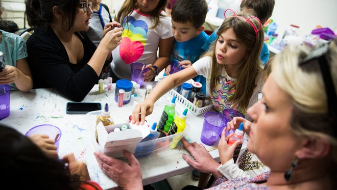 Hanna Sidwell, 7, reaches over her classmates for glitter to add to her slime on Tuesday, June 20, 2017, during summer camp at Center for Performing Arts Bonita Springs.