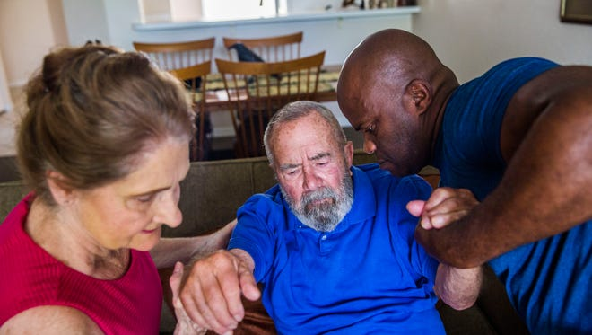 """With the help of caregiver Joseph Tanis, right, Linda Ragsdale, 75, helps her husband George Otto, 86, off the couch in his Naples home on Tuesday, June 20, 2017. The couple got married in 2008 and Otto was diagnosed with Alzheimer's disease in 2010. Ragsdale lives next door to her husband and gets assistance from caregivers. """"There are times when all I want to do is basically sit on the floor and cry because it's hard, very hard to understand what is happening in his brain,"""" Ragsdale says."""
