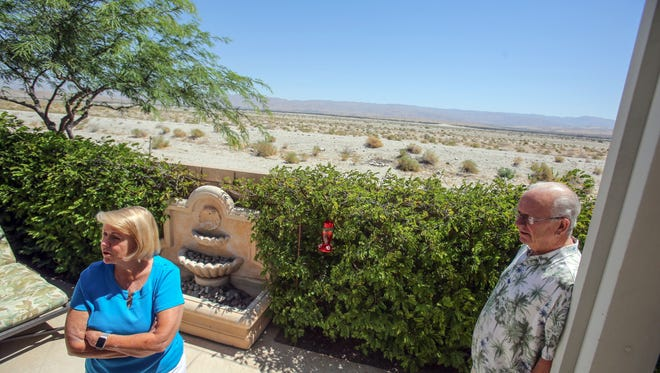 Jeri and Bill Barry, shown at their home in June, say they're satisfied with a new plan that will take the proposed CV Link path from atop the levee behind their Four Seasons home in Palm Springs and instead run it lower on the channel side of the berm.