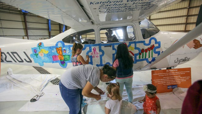 """Families paint a Cessna during a SafeLaunch """"Flights Above Addiction"""" event against substance abuse at Signature Flight Support at Palm Springs International Airport Saturday morning, June 24, 2017. SafeLaunch brings awareness to addiction through art."""